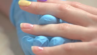 Applying of pink polish close up. Manicurist hand brushing pink varnish on client nails. Nail beautician in blue gloves doing manicure to female client in nail salon.