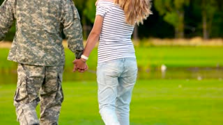 Army soldier reunited with wife, close up. Caucasian military man with girlfriend, back view.