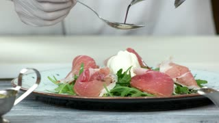 Arugula and prosciutto salad, sauce. Food preparation close up.