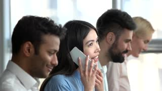 Asian girl hanging up a phone. Asian girl end phone call in office and keep working with a smile.