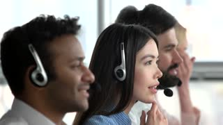 Asian girl working as dispatcher in office. Japaneese female dispatcher with colleagues, close up, side view.