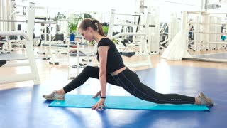 Athletic woman doing stretching at gym. Pretty girl doing split on mat at fitness club. Woman at fitness training.
