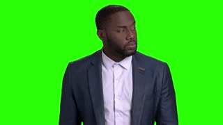 Attractive businessman waiting for someone. Serious afro american business person standing and looking aside with anticipation on green screen.