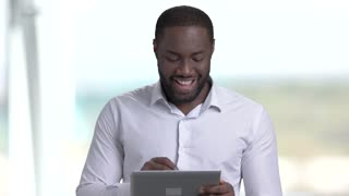 Attractive dark-skinned businessman using pc tablet. Smiling afro-american entrepreneur working on digital tablet on blurred background.