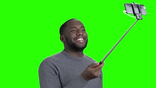Attractive man taking selfie with monopod. Young handsome dark-skinned man taking selfie on chroma key background. People, technology and lifestyle.