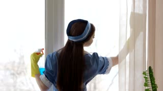 Attractive young housemaid wiping window. Slim female legs and windowsill.
