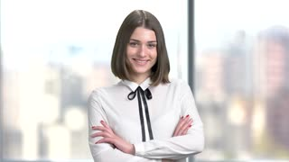 Attractive young lady with crossed arms. Happy smiling young business woman wearing white chiffon blouse on blurred background. Smiling young corporate.