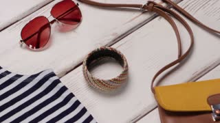 Aviator sunglasses and wicker hat. Woman's trendy hat on display. Colorful bracelet with fedora hat. Stylish sunglasses and headwear.