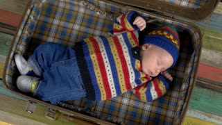 Baby in knitted sweater. Top view of sleeping child. Organic clothing for children.