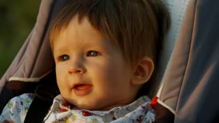 Baby smiling. Little boy in a pram.