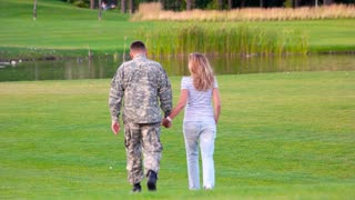 Back view military man on date in a park lawn. Happy soldier with woman on glade, rear view.