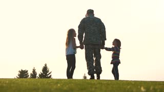 Back view soldier in uniform walk with daughters. Military man in camoubackgrounde walking holding hands of his little daughters.