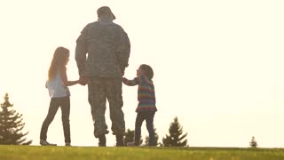 Back view soldier standing with two little daughters. Military man with kids outdoor in the evening.