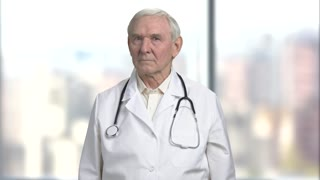 Bad news from the doctor. Portrait of an old serious nervous stressed doctor getting ready to tell bad news to a patient. Bright abstract blurred windows background with view on city.