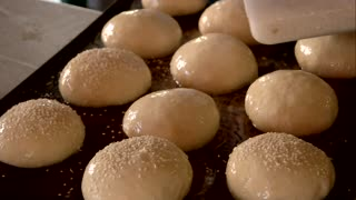 Baker sprinkles buns with sesame seeds. Set of unbaked buns on tray. Baking of healthy pastry. Healthy eating concept.
