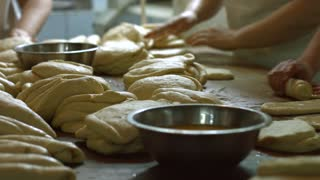 Bakers made bread. Women knead the dough on the table. Confectioners bake bread. Production of buns. Manufacture of bread.