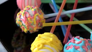 Ball-shaped sweets with glaze. Candies with colorful icing. Delicious dessert for children.