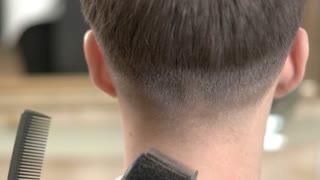 Barber using hair clipper, macro. Back of the head haircut.
