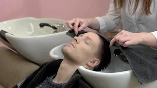 Barber wiping head with towel. Man and hair washing sink.