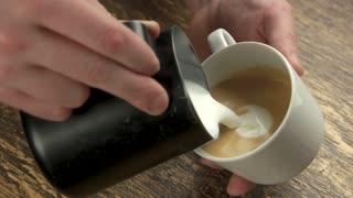 Barista making latte art bear. Frothy coffee in white mug.