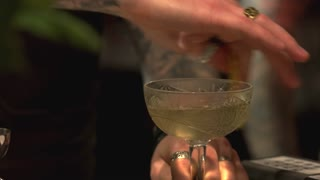 Barman adding lemon to the alcohol drink. Vintage glass of alcohol cocktail, close up.