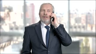 Bearded businessman talking on phone. Elderly man in formal wear talking on mobile phone, window city background. People, business, communication.