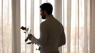 Bearded guy holding rose. Man looks out the window.