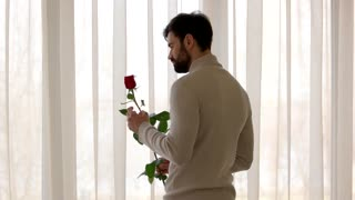 Bearded man holding rose. Guy near window. Love and wait.