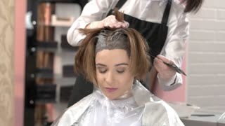 Beautician and client, hair dying. Pretty woman in beauty salon.