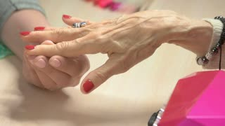 Beautician applying oil on manicured nails. Elderly woman receiving manicure and nail treatment in beauty salon.