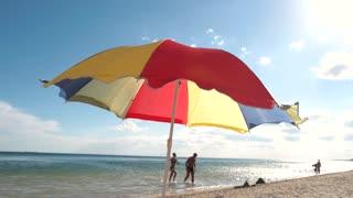 Beautiful bright umbrella flew away from a gust of wind. Beach season. Funny colorful beach umbrella. People bathe in the sea.
