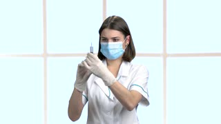 Beautiful brunette nurse with syringe. Female young doctor or nurse wearing a surgical mask holding up her hand with a syringe on abstract window background.