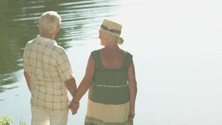Beautiful couple of seniors near water. Elderly people enjoying with nature in park. Happy summer time together.