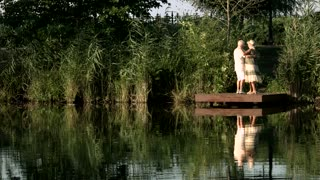Beautiful dance of elderly couple outdoors. Senior man and woman dancing romantic dance near lake, summer nature background. Love is endless.