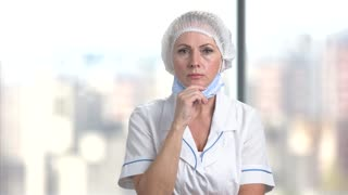 Beautiful female doctor looking shocked. Medical middle aged female doctor shocked and surprised. Bright blurred windows background.