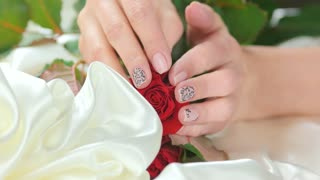 Beautiful female hands, roses, silk. Well-groomed young woman hands with gentle manicure caress fresh red roses on white silk fabric. Feminine care and sensuality.