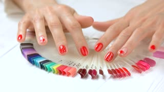 Beautiful manicured hands and nail samples. Young woman hands with perfect manicure and collection of nail color samples. Manicure for Saint Valentine Day.
