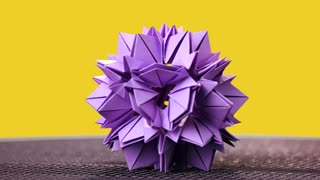Beautiful origami flower on yellow background. Floral paper decoration on colorful background. Kusudama work of modern design.
