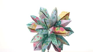 Beautiful origami patterned flower. Floral origami decoration isolated on white background. Beauty of paper folding.