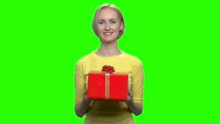Beautiful woman giving red gift box. Green hromakey background for keying.