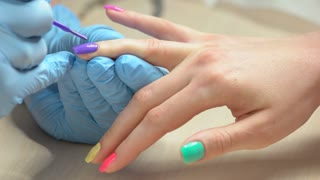 Beauty salon manicure workshop. Manicurist in blue gloves painting nail to client with purple color. Manicure master doing multicolored summer manicure in nail salon.