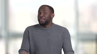 Black afro american man having fun. Portrait of happy self proud black man in sweater against bright windows background.