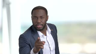 Black annoyed businessman pointing with finger. Irritted african-american entrepreneur arguing and indicating with finger on someone on blurred background.