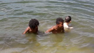 Black boy swimming in the river. Boys playing in the river.