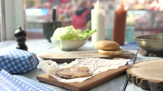 Black bun cheeseburger. Food and blurred cafe background. Tasty burger with chicken meat.
