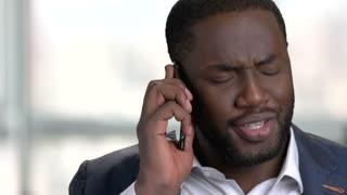 Black businessman having serious phone conversation. Bright blurred windows background.