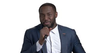 Black businessman in suit singing karaoke. Young afro american black guy with microphone against white isolated background.