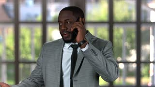 Black businessman phone talking. Man in a suit smiling. How to motivate employees.