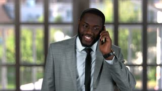 Black businessman talking on phone. Smiling guy indoors.