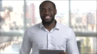Black handsome manager using digital tablet. Afro-american business trainer holding computer tablet and talking to camera.